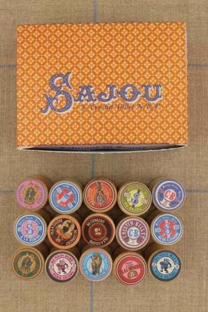 Box of fifteen small wooden bobbins with labels by Sajou