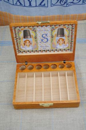 Wooden display case for spools and seven thimbles by Sajou